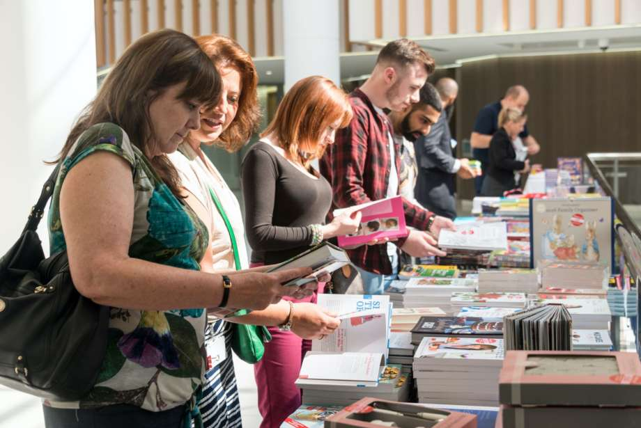 People Browsing Books from Stand